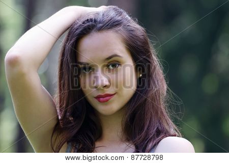 Close-up Face Of Beautiful Girl Straightens Hair With Her Hand With View Of Forest In Background Wit