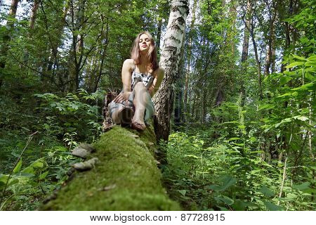 Beautiful Girl In Dress With Long Hair Sits Legs Stretched On Fallen Tree In Forest