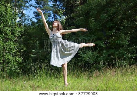 Beautiful Girl In Dress In Pose Of Swallows In Clearing In Woods On Summer Day