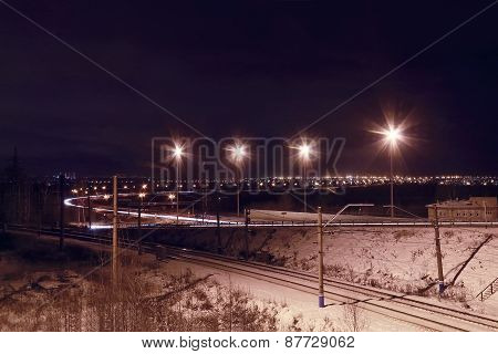 Night View Of Railroad With Lanterns And Lights Of City At Winter