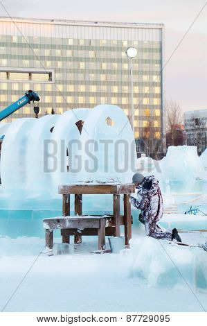 Perm, Russia - Dec 17, 2013: Man Carves Sculpture With Big Circles In Ice Town. Construction Of Ice