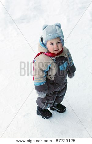 Little Boy Wearing Warm Jumpsuit Stands On Snow And Smiles At Winter