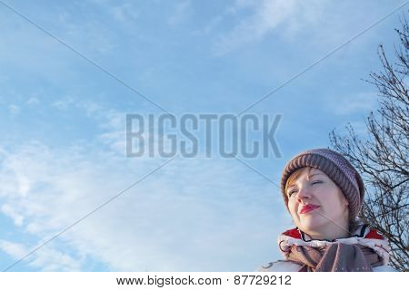 Portrait Of Young Beautiful Woman Looking Away At Winter Day At Background Of Blue Sky