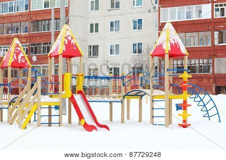 Colored Playground With Ladders And Slide Near Residential Building At Winter