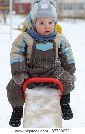 Little Boy Wearing Warm Jumpsuit Sits On Seesaw At Winter Day