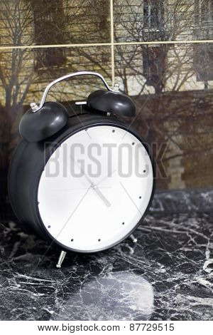 Stylish Black Alarm Clock On Marble Windowsill And View Of Trees Behind Glass