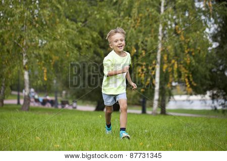 Happy Little boy running in autumn park
