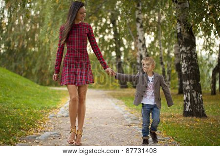 Happy Little boy and mother walking in autumn park
