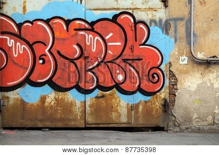 Colorful Graffiti Over Old Rusted Metal Gate