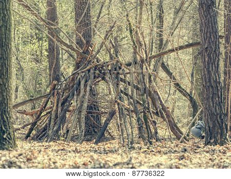 hut of branches in the forest.