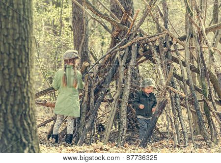 little girl with ter sister  in the wood near the hut. Photo in retro style