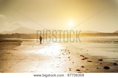 Surfer on the ocean beach at sunset on  Canary Islands. Lanzarote, Spain.