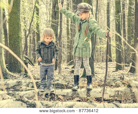 little girl in the forest with her sister. Photo in retro style