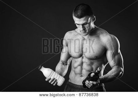 Sporty man in the gray background man holding a beer and milk and faces a choice,