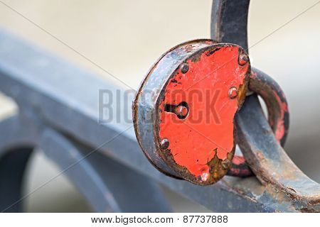 Padlock Of Red Color On An Iron Fence