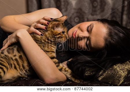 Young beautiful brunette holding a Bengal cat, dark bedroom