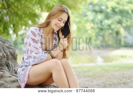young girl using tablet pc in the park.