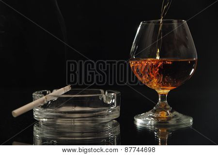 In a glass pour brandy, smokes a cigarette, black background