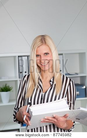 Woman In Striped Shirt Holding Binder In Office