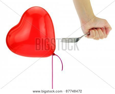 Fork about to pop a heart balloon isolated on white