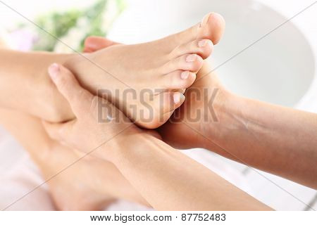 Masseuse massaging woman\'s foot.