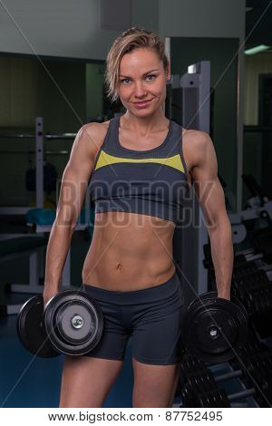 Beautiful, sexy, muscular blonde in the gym, holding a dumbbell in hands