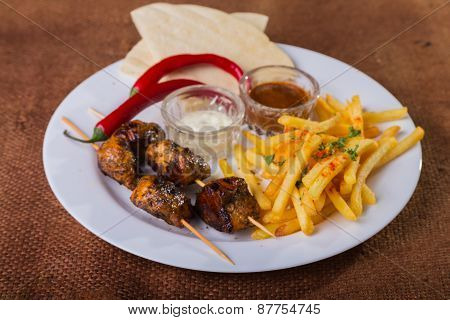 Skewers with french fries. Skewers of meat