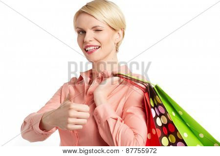 Woman holding shopping bag and showing ok, isolated on white background