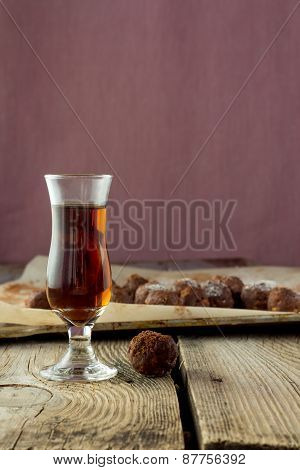 Small Glass Of Liqueur And Homemade Candies On Wooden Table