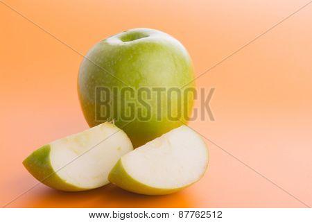 Green apple with slices on gradient orange background