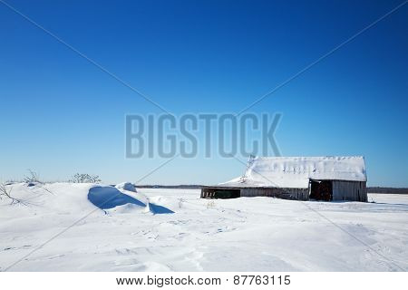 Old wooden barn in Quebec province of Canada. Rural snow scene with snow drifts and blue sky. SPace for your text.