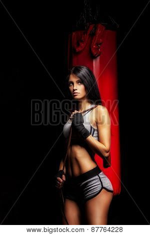 woman boxer near red punching bag