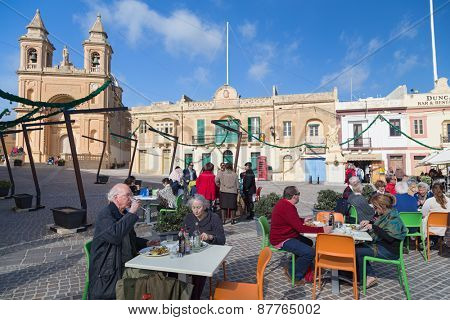 MARSAXLOKK, MALTA - JANUARY 11, 2015: People eating at restaurant terrace in front of the Parish Church of Our Lady of Pompei.