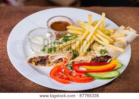 Dish in white plate with Shawarma , fries potato and sauces