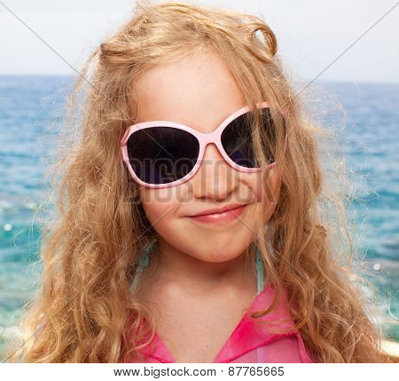 Child on beach. Girl in sunglasses on the sea