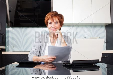 Happy businesswoman with documentation at home