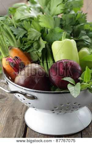 Red onion, beetroot, green pepper, carrot, basil, and celery in a colander