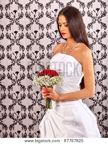 Sad bride in wedding dress on wallpapers bachground.