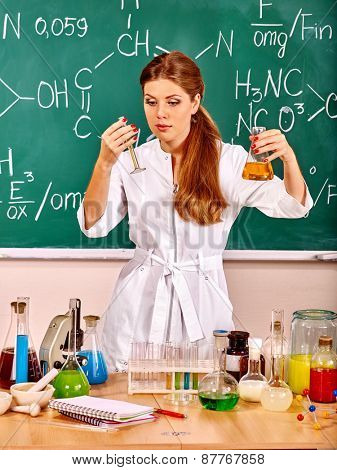 Chemistry female teacher with test-tube at classroom.