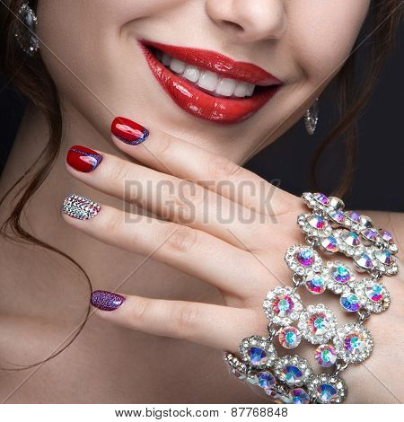 Beautiful girl with a bright evening make-up and red manicure with rhinestones. Nail design.