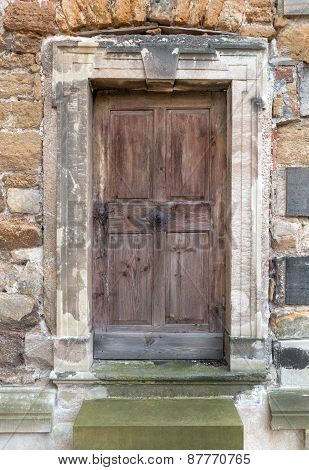 Old wooden door in a stone portal