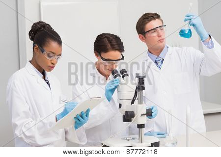 Scientists working attentively with microscope and beaker in laboratory
