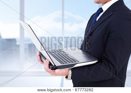 Businessman with watch using tablet pc against bright white room with windows