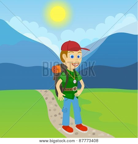 Young man tourist with a backpack standing on a path at the foot of the mountain
