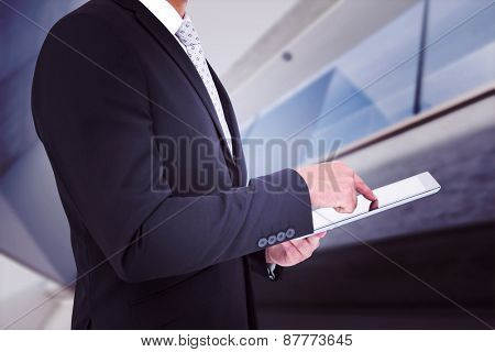 Businessman using his tablet pc against modern home with large windows