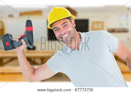 Smiling repairman holding power drill against workshop
