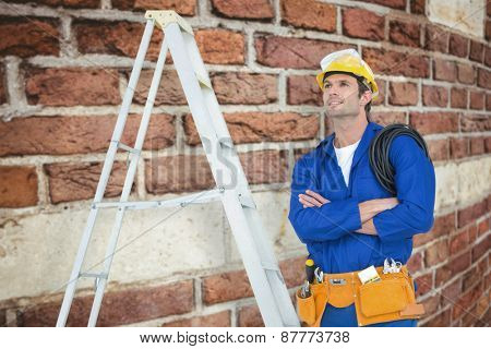 Thoughtful electrician with arms crossed by ladder against red brick wall