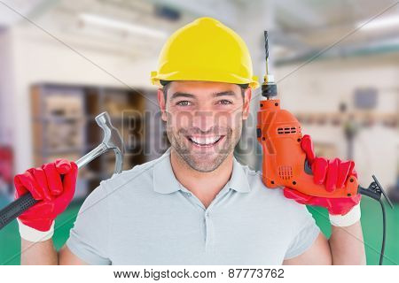 Happy repairman holding hammer and drill machine against workshop
