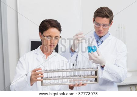 Scientists looking attentively at test tubes in laboratory