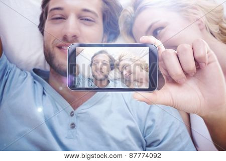 Hand holding smartphone showing against happy couple relaxing on bed